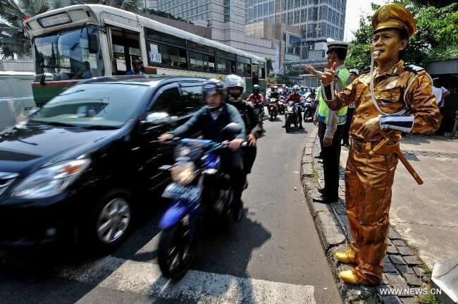 Seorang polisi berseragam biasa dan seorang polisi berkostum seperti patung