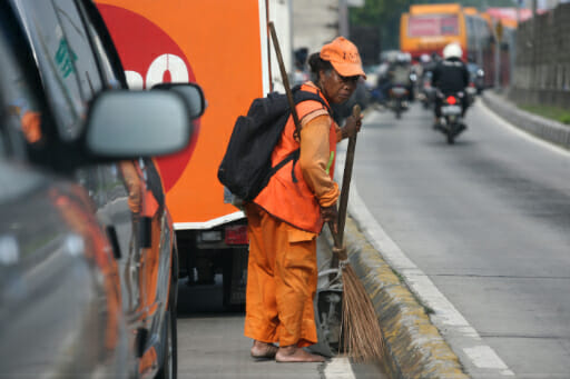 Petugas kebersihan jalan menyapu sampah-sampah di jalan.